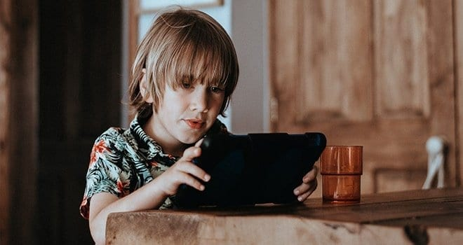 Boy with e-reader learning to read
