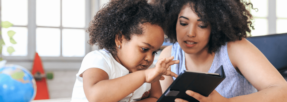Carer and young girl looking at ipad